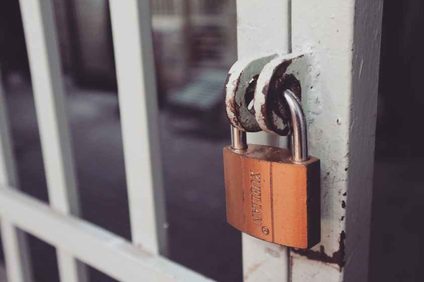 closeup photography of white gate with brass colored padlock